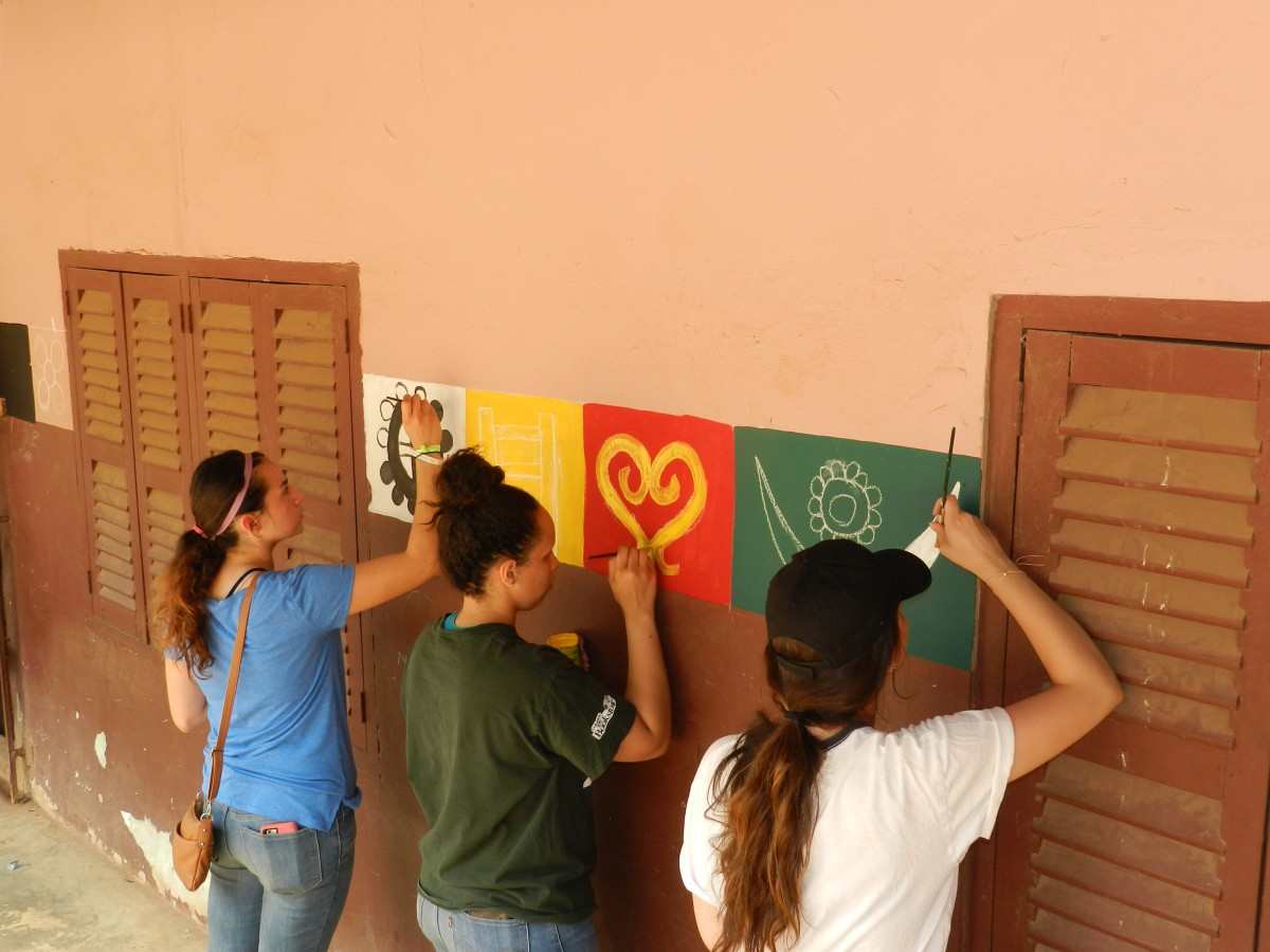A group of ethnic studies students painting wall mural abroad